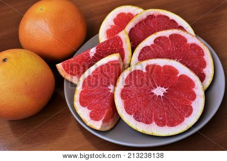 Fresh grapefruit slices on the grey plate and two grapefruits near.
