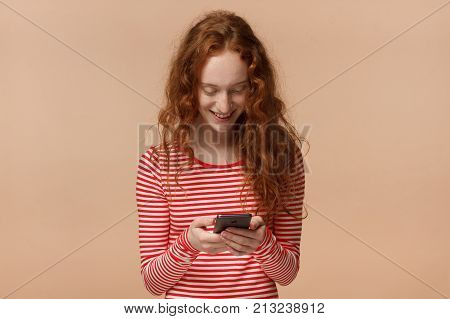 Indoor Picture Of Young Good-looking European Woman With Red Loose Curly Hair Isolated On Peach Back