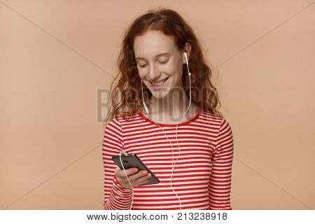 Indoor Closeup Of Good-looking Redhead Teen Girl Isolated On Peach Background Listening To Music On