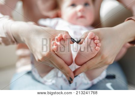 On the lap of a loving mother lies a newborn baby with fluffy little hair, mother gently supports the bare feet of the child with her hands, mother in a pink shirt and blue jeans, mother with a small son on the sofa concept of maternal love