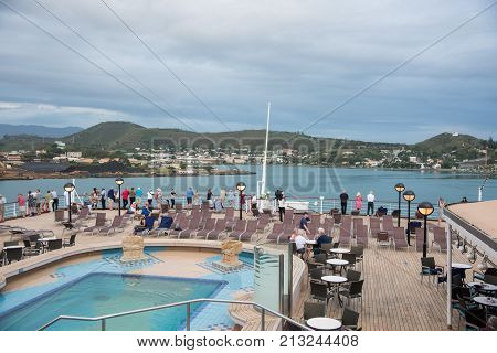 NOUMEA, NEW CALEDONIA, PACIFIC ISLANDS-NOVEMBER 25TH, 2016: Tourists on cruise ship deck with view into the waterfront architecture and island landscape under a cloudy sky in Noumea, New Caledonia