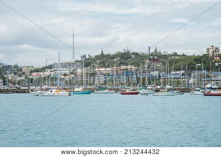 NOUMEA, NEW CALEDONIA, PACIFIC ISLANDS-NOVEMBER 25TH, 2016: Variety of sailboats anchored along the waterfront with architecture and island landscape in Noumea, New Caledonia