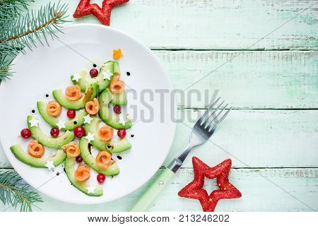 Healthy Christmas appetizer snack - avocado salmon cranberry Christmas tree top view