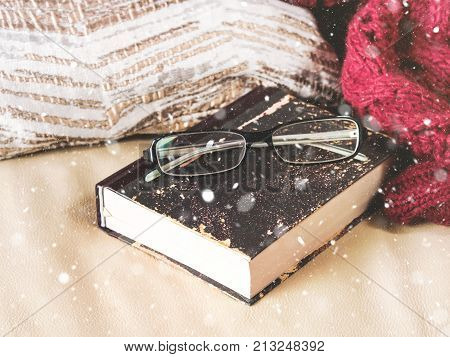 Reading Glasses and book, planning organizer on leather sofa. Christmas holidays planning or relax