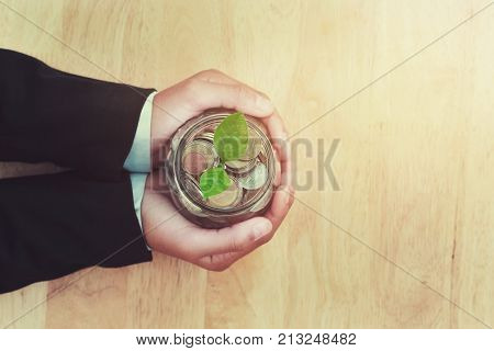 plant growing with coins in glass jar and hand holding bussiness saving money finance concept