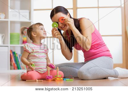 Kid girl and her mother have a fun playing together with puzzle toys. Young woman and child toddler sitting on floor and laughing.