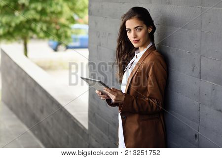 Businesswoman With Tablet Computer Standing Outside Of An Office Building.