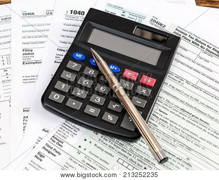 Tax form with calculator and pen on the table. Business concept.