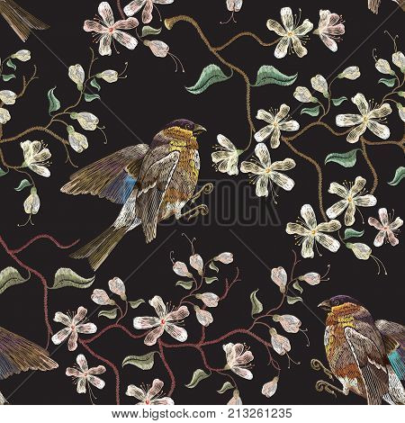 Embroidery birds and blossoming white cherry seamless pattern. Classical embroidery titmouse birds on branch blossoming sakura. Spring fashion pattern template clothes t-shirt design