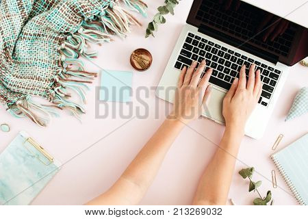 Flat lay home office desk. Female workspace with laptop eucalyptus branch accessories on pink background. Top view feminine background. Lifestyle blog hero.