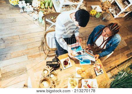 View from above of young black race woman and caucasian young man photographers co-working while having breakfast at agency