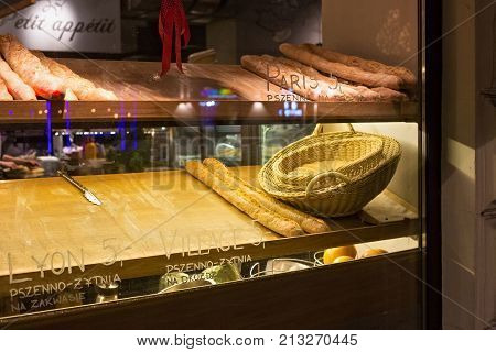 WARSAW, POLAND - JANUARY 02, 2016: Selling of French baguettes in a small restaurant in the center of Warsaw. Night view from street to showcase.