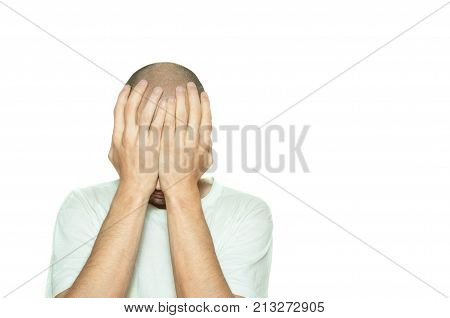 Young depressed man suffering from anxiety and feeling miserable cover his face with his hands and leaning on the white wall isolated