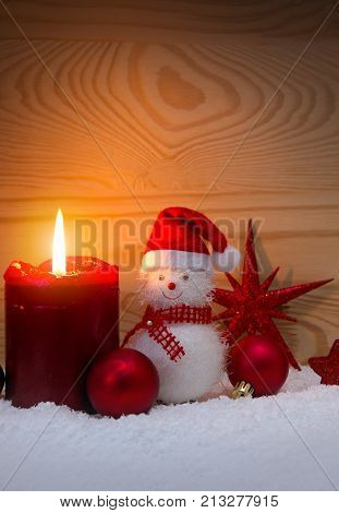 Christmas snowman with red scarf and santa claus hat , isolated on wood background.Advent candle and Snowman.