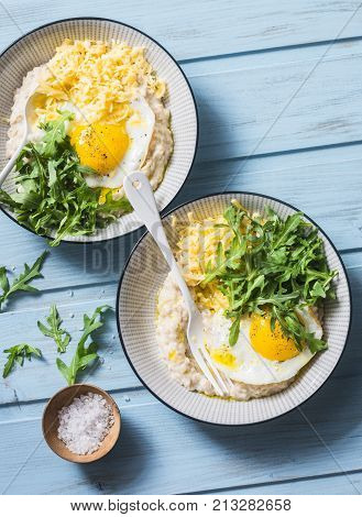 Cheese savoury oatmeal with fried egg and arugula on a blue background top view. Healthy balanced breakfast food