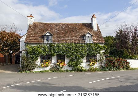 Stratford, UK: October 14, 2017: Beautiful, traditional old English cottage with red tiled roof, climbing clematis, and window boxes near Stratford upon Avon in England on a sunny da
