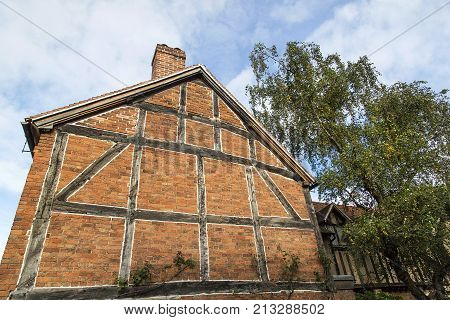 Gable end wall of a traditionally built Elizabethan half timbered, red brick house in Stratford upon Avon, England