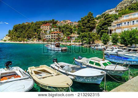 Typical mediterranean houses and fishing harbor with motorboats, Makarska riviera, Brela, Dalmatia, Croatia, Europe