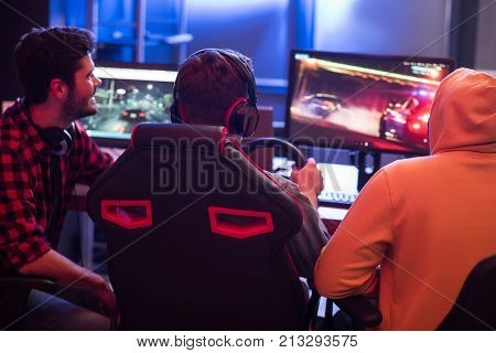 Back view of young gamers are sitting at home and enjoying car racing video game on computer. Focus on concentrated guy in headphones with steering wheel. Modern monitors in background