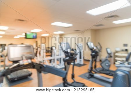 Blurred image of fitness center with cardio machines weight strength training equipment TV and large mirror. Empty gymnasium facility service room in 3-star hotel in Texas USA. Active lifestyle poster