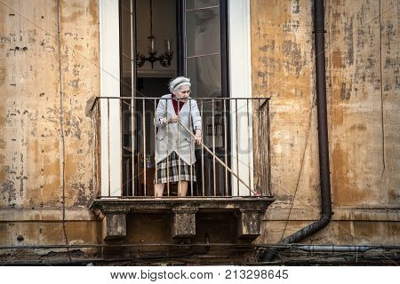 CATANIA, ITALY. April 3, 2015: An old italian woman is sweeping with a broom on her balcony. Historical building in the city center of Catania. Sicily, Italy.