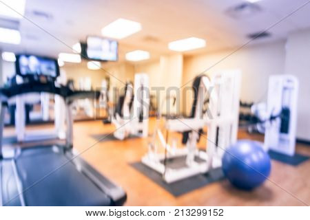 Blurred fitness center with cardio machines weight strength training equipment medical ball large mirror. Empty gymnasium facility service room hotel in Texas USA. Active lifestyle. Vintage tone poster