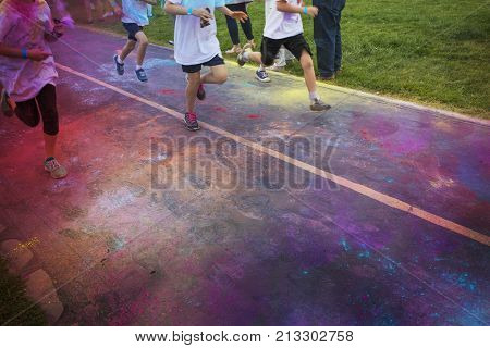 Abstract photo of a group of runners running in a color run race event. No faces visible on the legs and the feet and shoes of the runner. Lots of colorful clouds of chalk in the air and on the street