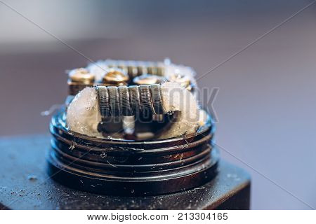 Rebuildable dripping atomizer or RDA for vaping or e-cigarette with Alien Clapton coil and cotton stripes wetted with e-liquid, modern vape device for quit smoking, macro photo with selective focus
