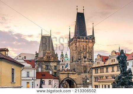 Malostranskie bridge towers (Lesser Town Bridge Tower) on the Charles Bridge in Prague in the Czech Republic at sunset in autumn. Sculptures and lights on the Charles Bridge