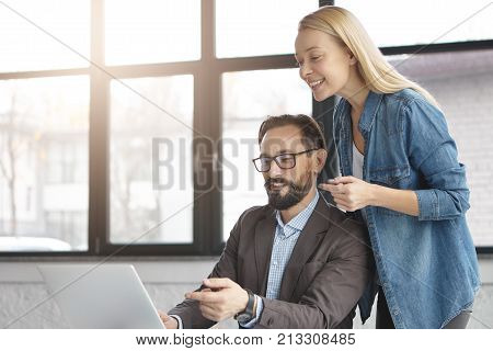Business Affairs Concept. Bearded Male Executive Officer Sits In Front Of Opened Laptop And His Secr