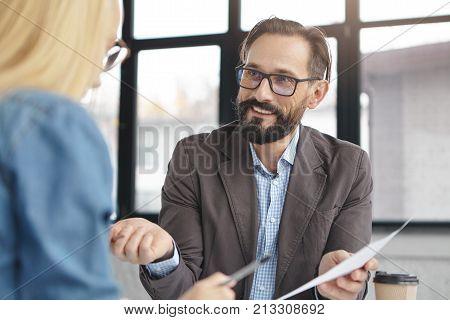 Portrait Of Elegant Handsome Bearded Male Enterpreneur Holds Document, Shows To His Secretary Things