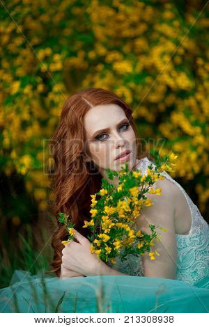 beautiful young girl with red hair in a lavish dress walking in the nature with flowers