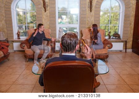 At the psychologist. A young couple is sitting on the edges of the couch, swearing, the doctor is sitting in the chair. Close-up of a psychologist in a brown chair.