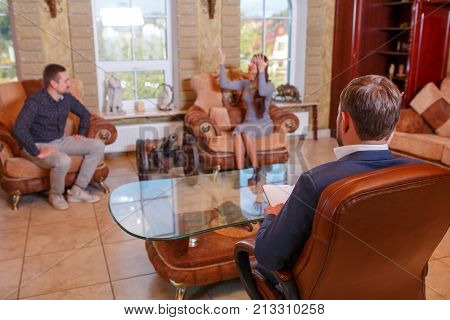 At the psychologist. A young couple is sitting on the couch, swearing, the girl is waving her hands, the doctor is sitting in the chair, taking notes.