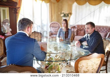 At the psychologist. A young couple is sitting at a table, listening to a psychologist who sits in a chair, anesthetizing them.