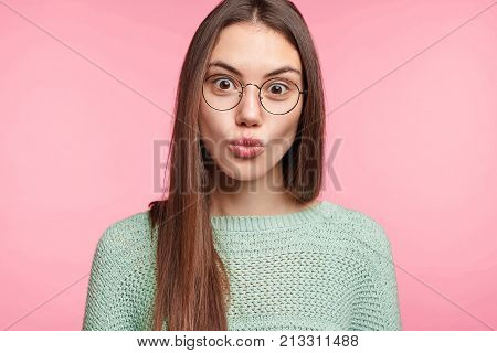 Pretty Brunette Asian Female Model With Rounded Lips, Looks In Astonishment Into Camera, Has Puzzled