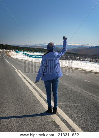 Hitchhiking tourism concept. Travel hitchhiker woman stand on road during holiday travel. Raised hand to stop the car.