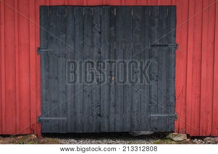 a double black barndoor on a red barn