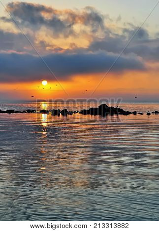 Evening seascape at black sea and orange sky above it with golden reflection on calm waves. Amazing sunset on the beach