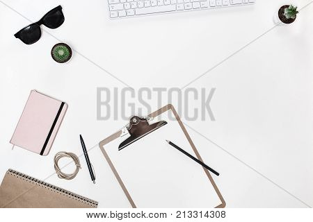 Modern white blogger's desk table with white keyboard, folder tablet, cactus and pink diary. Top view with copy space, flat lay, scandinavian design.