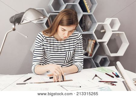 Portrait of serious young good-looking female architect sitting at her workplace, making drawings with pencil and ruler, trying not to make a mistake in blueprints
