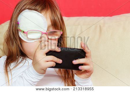 Childhood childcare being polite concept. Little toddler girl with bandage on eye playing games on smartphone