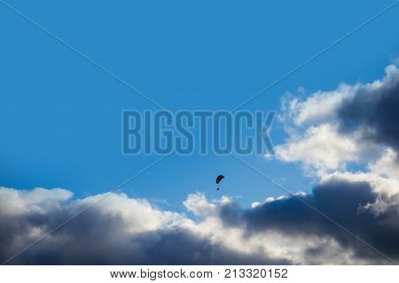 Passionate about Aeronautics people - Daring paraglider flying high in the clouds. Air sport and recreation. A powered glider with a dorsal power plant, providing the rise and moving in the air.