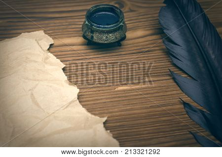 Blank letter page with copy space. Writer desk table. Blank crumpled paper page black feather pen and inkwell on table background. Education background.