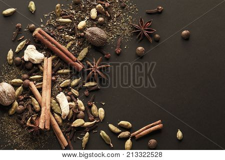 A set of oriental spices, seasonings for aromatic cocktails and dishes on a black background. A template for a label, an article, a recipe, a signboard. Top view.