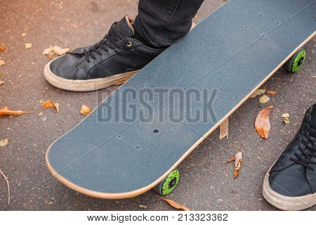 Close-up of a skateboarder's foot in black krosovkah on a skateboard, among the autumn leaves, a skate in the middle of the skateboarder's feet. The concept of sport.