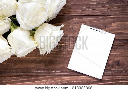White roses with empty white paper on the wooden table. Original romantic wallpaper for the desktop.
