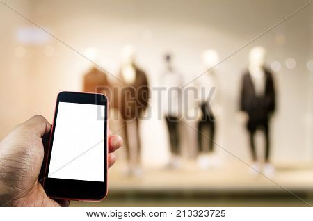 blank screen mobile phone in hand with blurred image of men fashion clothes shop showcase in shopping mall background internet connection communication technology and shopping online concept