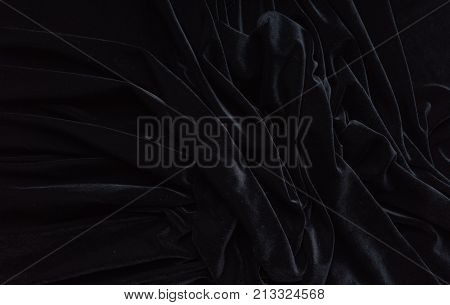 Dark black velvet fabric, wave, draperies. Beautiful textile backdrop to create creative layouts for black Friday. Close-up. Top view