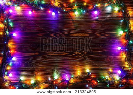 Wreath and garlands of colored light bulbs.Christmas background with lights and free text space. Christmas lights border. Glowing colorful Christmas lights on wooden background. New Year.